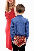 un enfant offre des chocolats pour la fête des mères