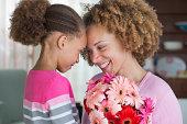 une enfant offre des fleurs à sa mère pour la fête des mères